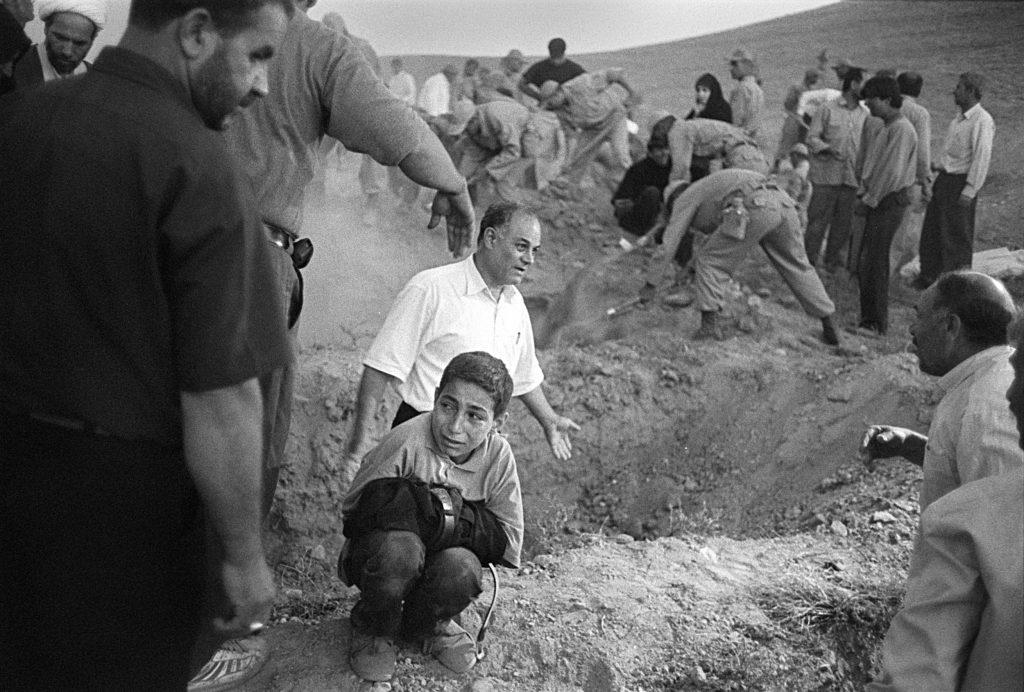 IRAN'daki askerler ve köylüler, deprem kurbanları için mezar kazıyorlar. Bir çocuk gömülmeden önce babasının pantolonunu tutuyor. Fotoğraf: Eric Grigorian, ABD)