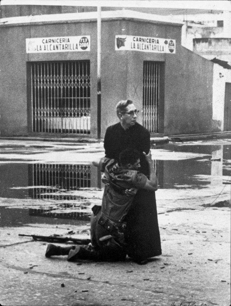 1962. Bir keskin nişancı tarafından vurulan asker son nefesinde bir papaza sarılıyor. Fotoğraf: Héctor Rondón Lovera, Venezuela