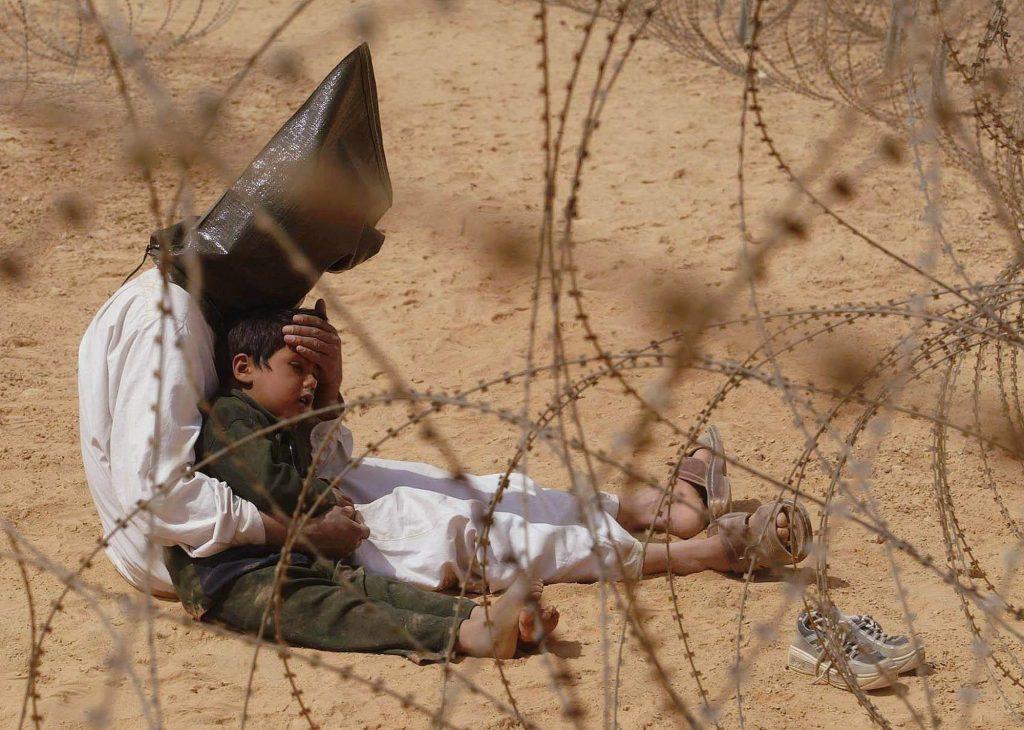 2003 Irak savaş esiri çocuğunu sakinleştirmeye çalışıyor. Fotoğraf: Jean-Marc Bouju, Fransa