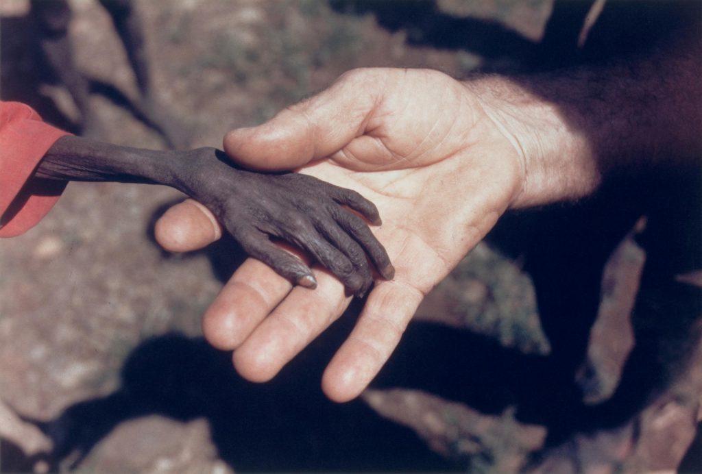 1980. Uganda'da açlıktan ölmek üzere olan bir çocuk ve bir misyoner. Fotoğraf: Michael Wells, İngiltere